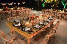 Montaje para boda campirana con mesas y sillas de madera y centros de mesa con…