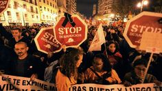 """Protesters hold placards reading """"Stop evictions"""" as they attend a demonstration during a general strike in Valencia, November 14, 2012."""