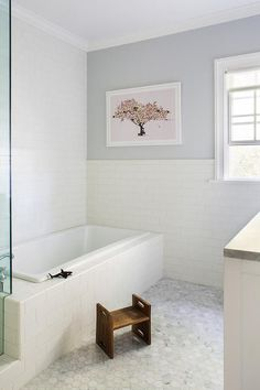 Beautiful white and gray boy's bathroom is glad in large marble hexagon floor tiles  and boasts a subway tiled drop in tub placed against a wall covered in white subway tiles and a gray painted wall with a subway tile trim holding a tree print in shades of pink beside a window.