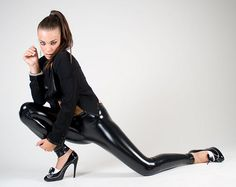Model in wet-look leggings, all black, interesting pose