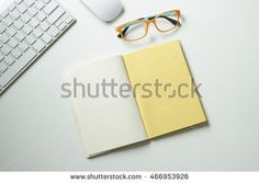 top view, office accessories keyboard ,yellow book, orange glass and white mouse on the table