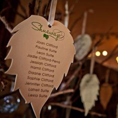 Leaf shaped seating cards hung from a rustic vase of branches. Natural theme wedding designed by Event planner A Stylish Affair, Okanagan. Stationary by Modern Invitations, Kamloops