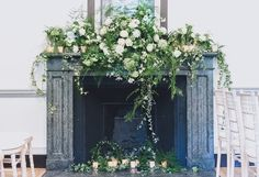 Bridal flowers by Okishima & Simmonds London O&S. www.okishimasimmonds.com Fireplace arrangement with candles. Neutral white green natural ivy fern trailing fireplace garland hearth tea lights dahlia roses lisianthus freesia viburnum gelder roses wild free unconstrained foliage