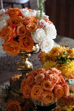 Orange and white roses and yellow mums top an antique mirrored table.
