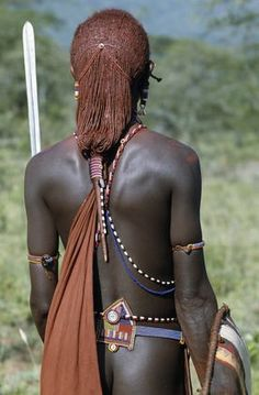 Africa | A back view of a Maasai warrior resplendent with long ochred braids tied in a pigtail. This singular hairstyle sets him apart from other members of his society. Kajiado, Kenya | © Nigel Pavitt