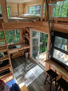 The cabin includes two queen lofts, a 4-burner gas stovetop, refrigerator/freezer, hot indoor shower, outdoor shower, indoor composting toilet, drinkable and running water, and an indoor/outdoor bar.