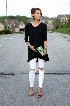 Long black tunic over distressed white denim, palm print clutch, nickel and suede leather earrings