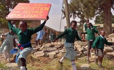 Works democratically with peers: Delighted schoolchildren  run into the playground after breaking the wall illegally erected around it