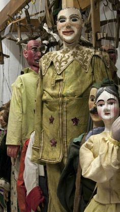 Marionette Puppets appear to be antique hanging in storage.  history of puppetry craftmanship puppetmaking puppet design glasseyesonline.com
