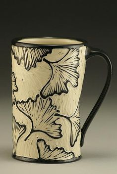 Ginkgo Mug by Jennifer Falter. Wheel thrown porcelain mug with graceful ginkgo leaves. The surface of this mug is hand carved through a layer of black slip to create a contrasting and textural surface, using a technique known as sgraffito. Each piece is unique. Size and design may vary slightly from image shown. Signed on the bottom. This mug holds approximately 16 oz. Dishwasher and microwave safe.