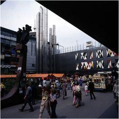 Piazza met de 'Pijpen', rechts tussen het winkelend publiek een draaiorgel. Foto: Bijvank, G.J.- 1975