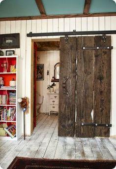 Love this rustic wood door divider.