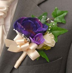 A grooms artificial Wedding buttonhole with a ivory Emma rose   a silk purple freesia and a silk purple anemone.  With loops of pearls, spray of ivy leaves and a   ivory grosgrain ribbon bow and stem.    Measurements  Width:- 3.5 inches  Length:- 7  inches (Including stem and top of ivy)    Groom's buttonhole from Sarahsflowers