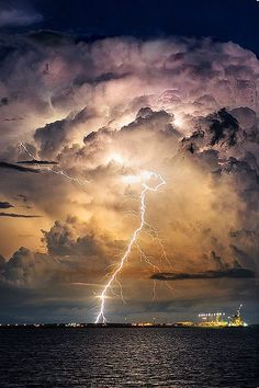 Dark sea and sky lit up with the flash of a lightning bolt between the clouds and water. All Nature, Science And Nature, Amazing Nature, Tornados, Thunderstorms, Thunderstorm Clouds, Cool Pictures, Cool Photos, Beautiful Pictures