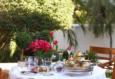 mesa de chá com porcelana antiga dourada, jogos americanos em crochet, peças artesanais, com flores e verdinhos artificiais no jardim da casa da minha mãe