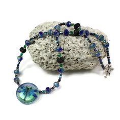This glass dragonfly necklace is a gorgeous and sparkling statement piece made up of blue, green and black Czech glass, black lava beads and silver.