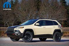 Jeep Cherokee Canyon Trail - Jeep Cherokee gana en capacidades con una selección de accesorios y partes Mopar que lo convierten en un vehículo incomparable fuera de la carretera. El matiz 'Desert Tan' se acentúa con un cofre negro satinado y un vinil  conmemorativo de uno de los senderos más representativos de Moab.