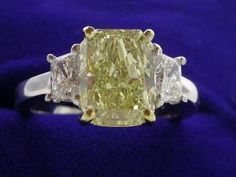 Diamond ring with 2.70 carat cut-cornered rectangular modified brilliant (radiant) cut graded Natural Fancy Yellow color, SI1 clarity, depth 66.7%, table 65%, Good polish, Good symmetry, No fluorescence, measuring 9.13 x 6.93 x 4.62 mm (ref: GIA 15060910, dated 06/08/2006) set in a custom14 karat white gold three stone mounting with a pair of matched trapezoid diamonds with 0.77 total carat weight set in basket style heads. The center stone is set in a 14-karat yellow gold head.