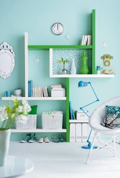 White and green shelves installed as a library alcove lined with floral wallpaper