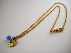 Colgante engarzado con cadena de 40cm de longitud con pieza dorada en forma de concha y jade azul // Pendant with chain 40cm in length with gold piece shell and blue jade