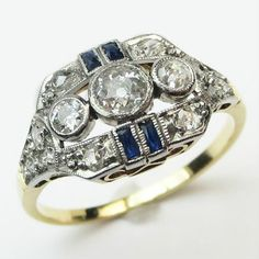 The Dashing Ring:  Three old European cut diamonds totaling about .25cts nestle in platinum bezels tucked into a framework resplendent with tiny rose cuts, accent sapphires, and milgrain.   Ca.1920  Maloys.com