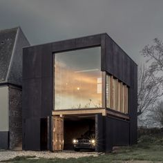 A blackened plywood box connected to one end of a rural home on France's…