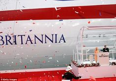 Celebration: Red white and blue confetti rains down on the Queen after the bottle is smashed