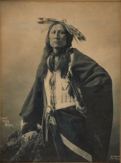 "Lone Bear, Oglala Lakota. Photo by Frank A. Rinehart, Omaha, Neb., 1898. A ""4-Directions"" quill-wrapped wheel decorated with hawk feathers is tied into Lone Bear's hair. He wears a beaded vest and holds a cluster of arrows. The tip of his bow is leaning in the left foreground. Heritage Auctions. 2009 September American Indian Art Auction #6029"