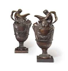 A NEAR PAIR OF BRONZE EWERS AFTER THE MODEL BY JOHN FLAXMAN SR., FRENCH, LATE 18TH EARLY 19TH CENTURY. Of antique-form, with a handle in the form of a Triton, with laurel swags and dolphin masks.