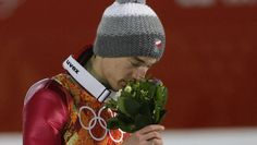 Poland's gold medal winner Kamil Stoch takes a smell at the flowers after the men's normal hill ski jumping final at the 2014 Winter
