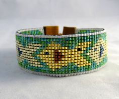 Bayou Woman loom-weave bead bracelet featuring red drum and speckled trout swimming in a sea of aqua-colored beads, fastened with an adjustable leather and silver bead closure.