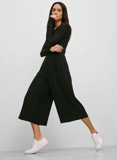 Black set with culottes and top, worn together with white simple sneakers.