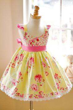 Beautiful Summer Girls floral handmade dress in rich yellow and pink tones. Lovely details including high quality cotton fabric, flutter sleeves and an eyelet lace hem.