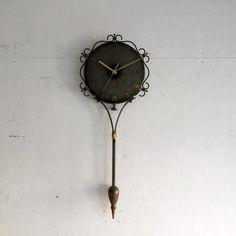 ヴィンテージの壁掛け時計 ミッドセンチュリーの壁掛け時計です! アイアンのボディーはフラワーモチーフにながーいフレームのユニークな形ですね。 文字盤に沿って淡いゴールドの花びらのペイントもまた素敵です。 壁にかけるだけで華やかになるアイテムです。ご自宅のにはもちろん、カフェやレストラン、洋服屋さん、どこでも目に止まる素敵なインテリアとして飾ってください!