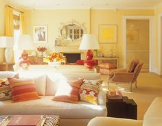 Back-to-back sofas in the living room are upholstered in different fabrics and separated by a sliver of a console that allows just enough room for two lamps and a bouquet. Above the pale, understated mantelpiece, a 1940s rococo mirror looks playful rather than formal. A mixture of subtly striped and geometric-pattern pillows and stacking tables from Hinson bring plush comfort to the sofa.   - HouseBeautiful.com