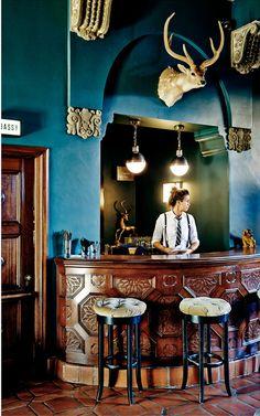 Terra cotta floors, carved mahogany bar, black stools, Turquoise walls ... wow!