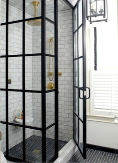 Amazing bathroom features a glass and steel shower walk in shower filled with…