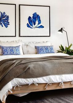Neutral bedroom with a pop of blue in the art and pillows: