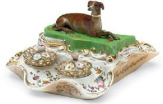 A JACOB PETIT PORCELAIN GREEN AND APRICOT GROUND ENCRIER MID 19TH CENTURY, BLUE J.P. MARK Modeled as a brown whippet recumbent on a shaped green mound, the shaped base painted inside and out with scattered flowers and curving to form two apertures fitted with separate inkwell and sander, each with reticulated gallery and flower-encrusted cover, the pen tray as a similarly shaped and painted dish extending on the other side