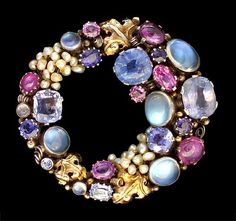 Dorrie Nossiter. Brooch, open elliptical circular/crescent form, with wire-scrolls and leaves. Silver, gold, moonstone, sapphire, ruby, seed pearl, c. 1930. H: 5.3 cm (2.09 in), W: 5 cm (1.97 in). Fitted case. Sold by Van Den Bosch. View 4 (other way up).