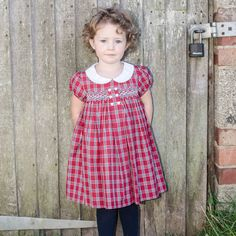 What a lovely tartan dress in a dazzling red. It's got cute little cap sleeves, six button detail on the smock and a contrasting white peter pan collar