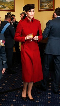 Catherine, Duchess of Cambridge drinking orange juice, paired the elegant outerwear, called 'Ami' from the high-street label's Autumn/Winter 2011 collection, with a dark brown bow-adorned hat by one of her favourite milliners, Lock&Co