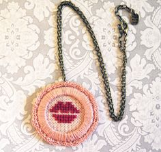 Cross stitch kiss lips pendant necklace. Embroidery necklace, Crochet, Pink, Antique chain. €18.50, via Etsy.