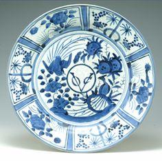 染付VOC花鳥文皿 古伊万里様式 (17世紀後期)/17世紀中期、それまでヨーロッパへ輸出してきた中国が明時代末期の動乱により、輸出できなくなり、その替わりとして、有田の焼物が輸出されるようになった。 見込みのVOCの文字は、当時、そのヨーロッパへの輸出を担っていたオランダ連合東インド会社(Verenigde Oostindische Compagnie)の頭文字を組合わせた社章であり、当時の輸出品にはこのVOCの文字の入ったものが多く造られている。 また、このような皿の縁部を窓絵にし、その中に文様を描くスタイルの皿を「芙蓉手」と呼ぶが、それは、芙蓉の花が開いたように見えることが由来であり、当時、最も好まれたスタイルであり、大小相当数の皿が造られ、輸出されている