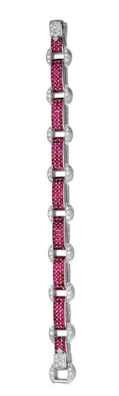 RUBY AND DIAMOND BRACELET, CARTIER,  CIRCA 1930.  Composed of a series of rectangular links set with calibré-cut rubies, connected by circular motifs set with single- and circular-cut diamonds, to a clasp similarly set, length approximately 190mm, partially numbered, signed Cartier.