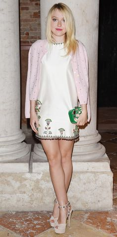Dakota Fanning was clad in head-to-toe Miu Miu at the Miu Miu Women's Tales Dinner, selecting an embroidered white satin shift (with a beaded fringe) that she styled with sequin-speckled pale pink cardi, a Kelly green gem-encrusted clutch, and nude bejeweled ankle-strap peep-toes. #InStyle