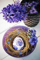 Osterei im Nest mit blauen Hornveilchenblüten in Serviettentechnik dekoriert