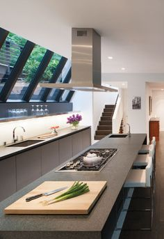 A long #island topped with #granite yields plenty of work space in this new #kitchen by Deborah Kalkstein of Contemporaria. Love the steam-lined look