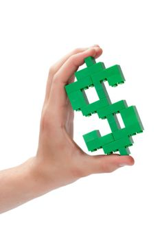 Human hand with lego dollar sign - Stock photo