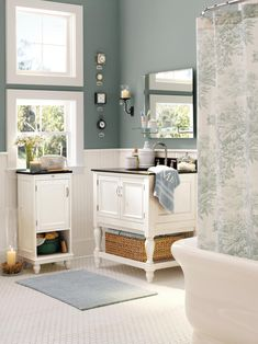 This bathroom is full of accessories from the retailer Pottery Barn including a shower curtain, clocks, candle sconces, and a small white vanity and coordinating cabinet.